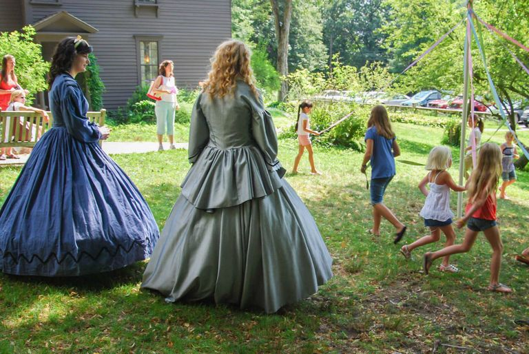 Two guides in historical dress at the Louisa May Alcott Orchard House Museum. Rewire PBS Little Women
