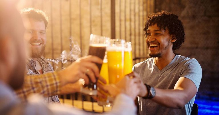 Young excited multicultural men celebrating and toasting with a beer in the sunny pub after work. Rewire PBS Living Healthy Habits
