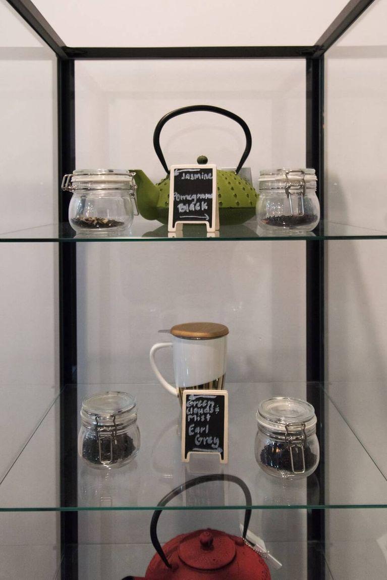 A display of tea pots and loose leaf tea on glass shelves. Rewire PBS Living Heritage Tea House