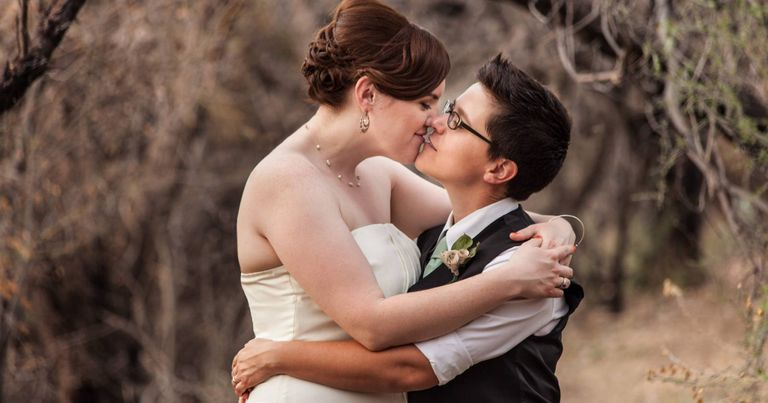 Happy same sex newlyweds kissing in the woods. Rewire PBS Living Wedding Planning