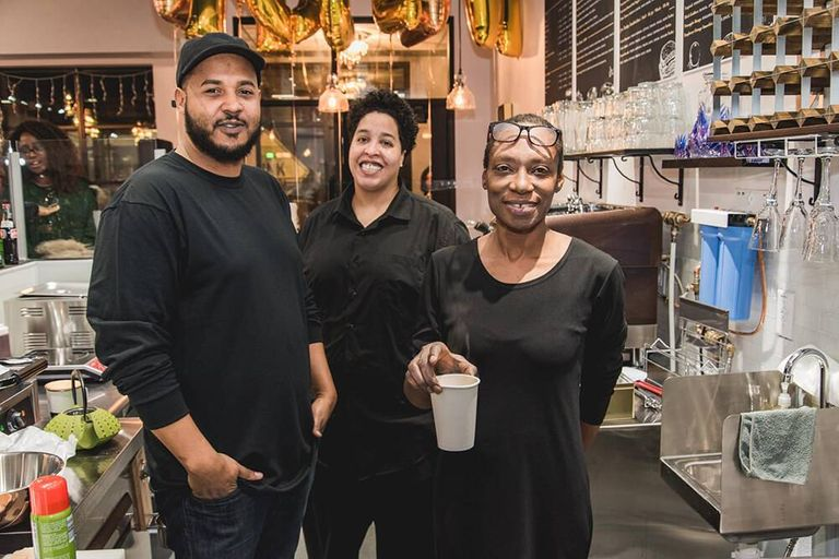 Two women and a man behind the counter of a tea house. Rewire PBS Living Heritage Tea House