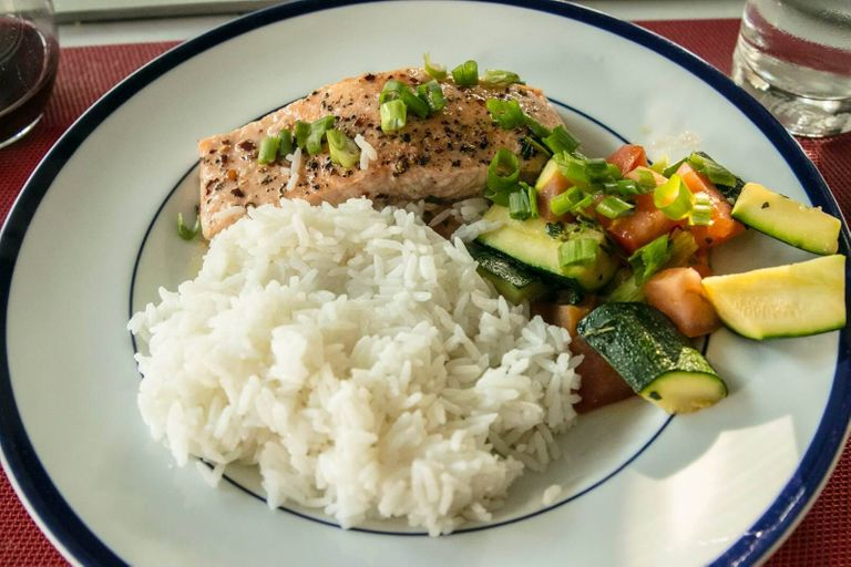 Rice, veggies, and salmon on a blue and white plate. Meal Kits pbs rewire