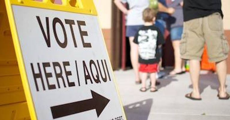 A line of people waiting next to a Vote Here / Aqui sign. Young Voters pbs rewire