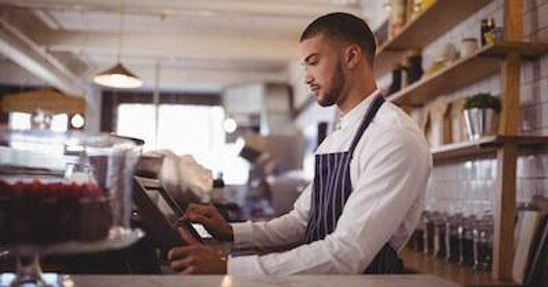 Young male barista taps at the point of sale at the cafe in which he works. Quit Your Job pbs rewire