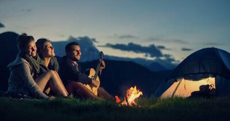 Three friends sit next to a fire and tent as one plays a song on a guitar. Too Much Time With Your Partner pbs rewire