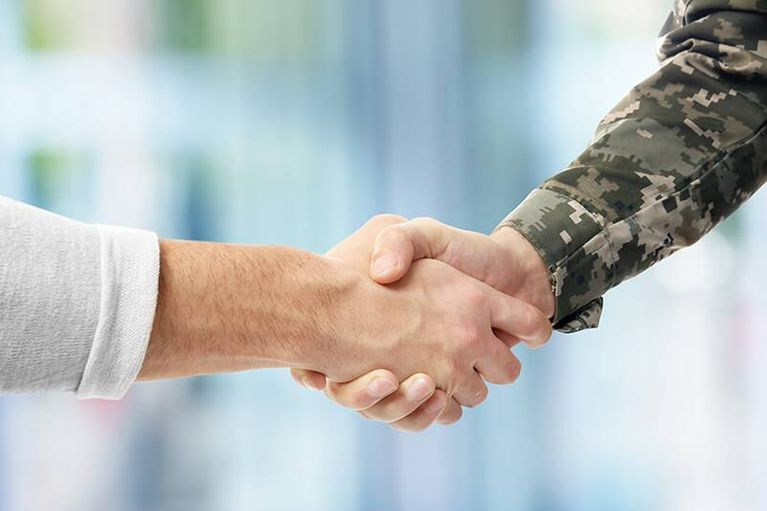 Soldier and civilian shaking hands on blurred background. Rewire PBS Our Future Draft