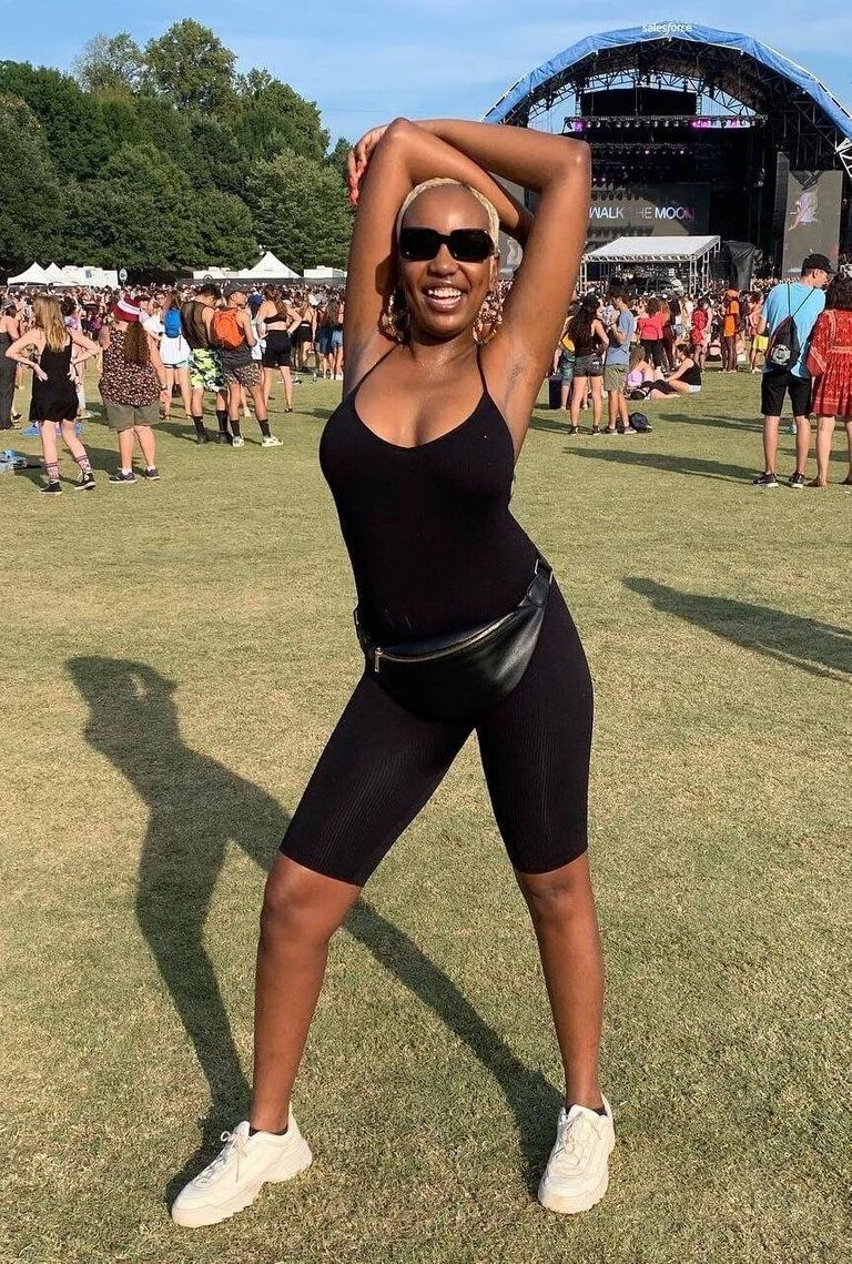 A young black woman in a black jumpsuit, fanny pack and sunglasses poses and smiles at a music festival. Rewire PBS Love Diabetic