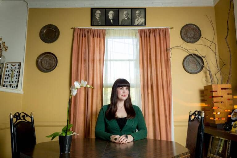 Photo of death-positive advocate and YouTuber Caitlin Doughty, a young woman with long black hair seated at a table. Rewire PBS Living Funeral
