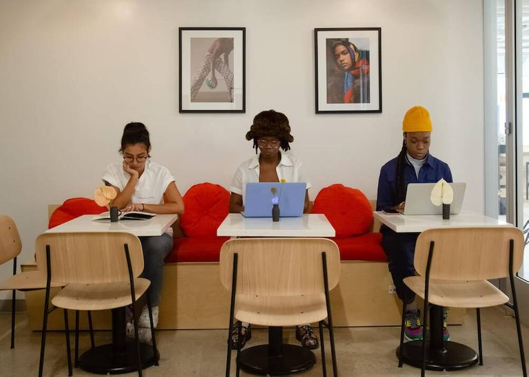 Photo of three people of color at work in a coworking space. Rewire PBS Work People of Color