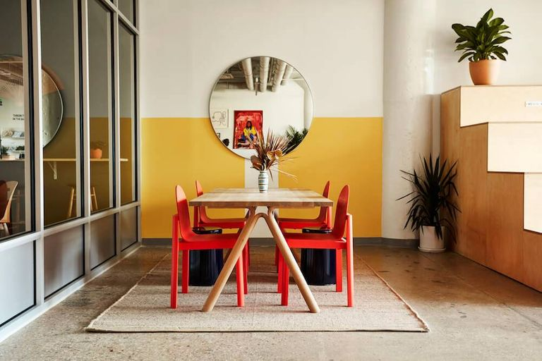 Photo of a breakout space with a wood table and red chairs in a coworking space. Rewire PBS Work People of color