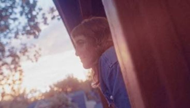 A photo of Katie Moritz leaning outside a window at sunset.
