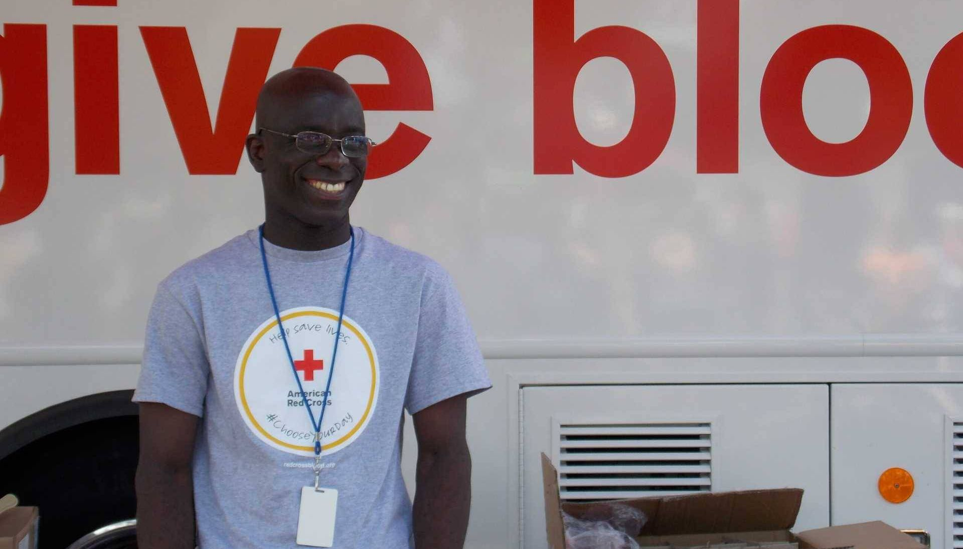 """Man dressed in grey t-shirt standing outside of a van that reads """"give blood"""""""