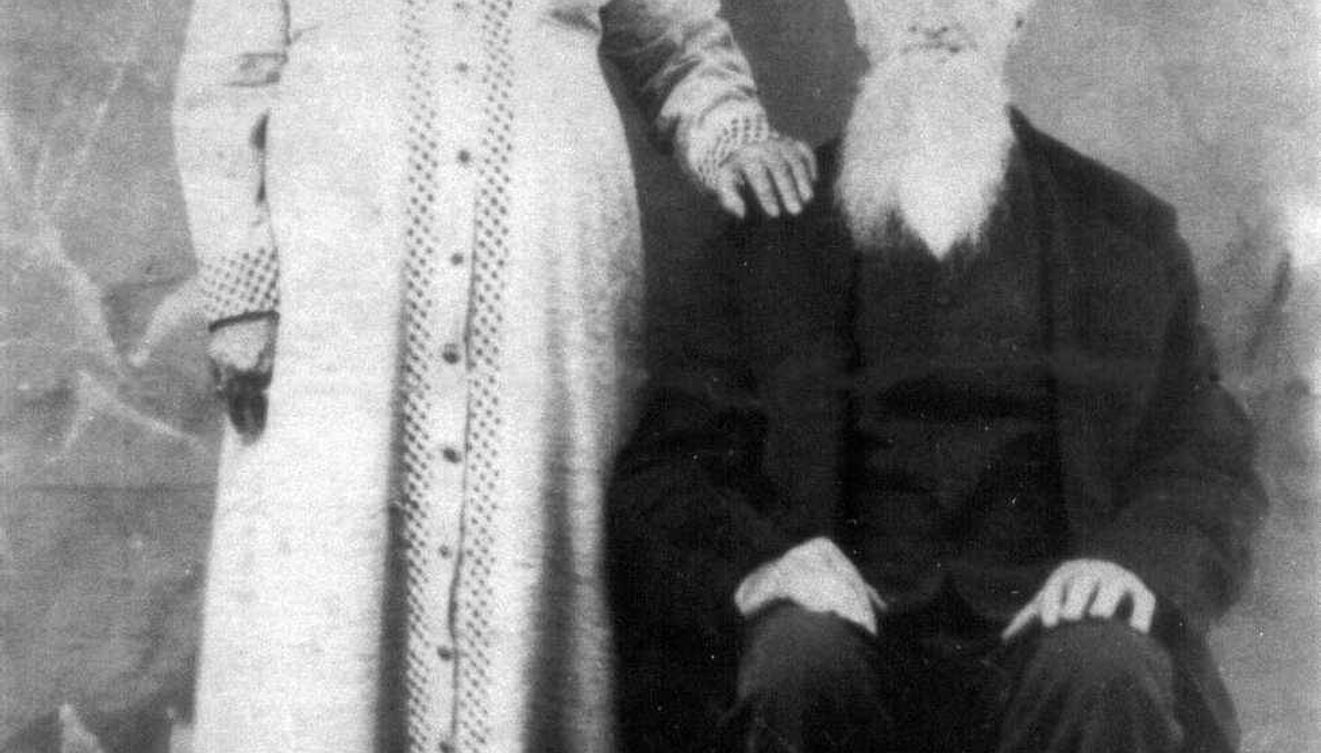 Woman dressed in white dress standing next to man who is sitting dressed in black overcoat.