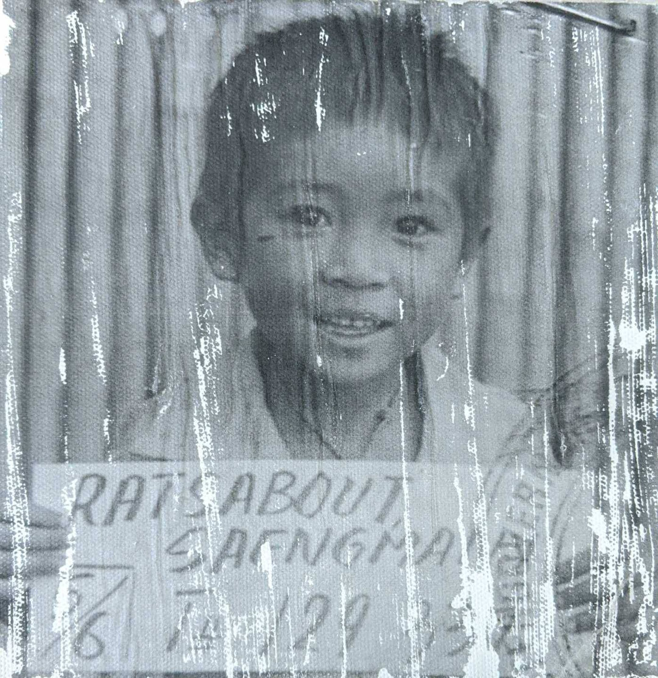 Child with smile holding sign that reads Ratsabout Saengmany