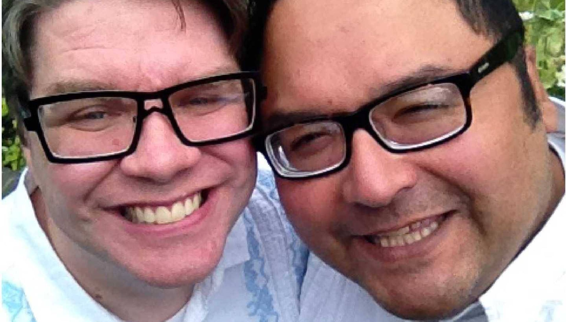 Two men dressed in blue shirts and glasses smiling
