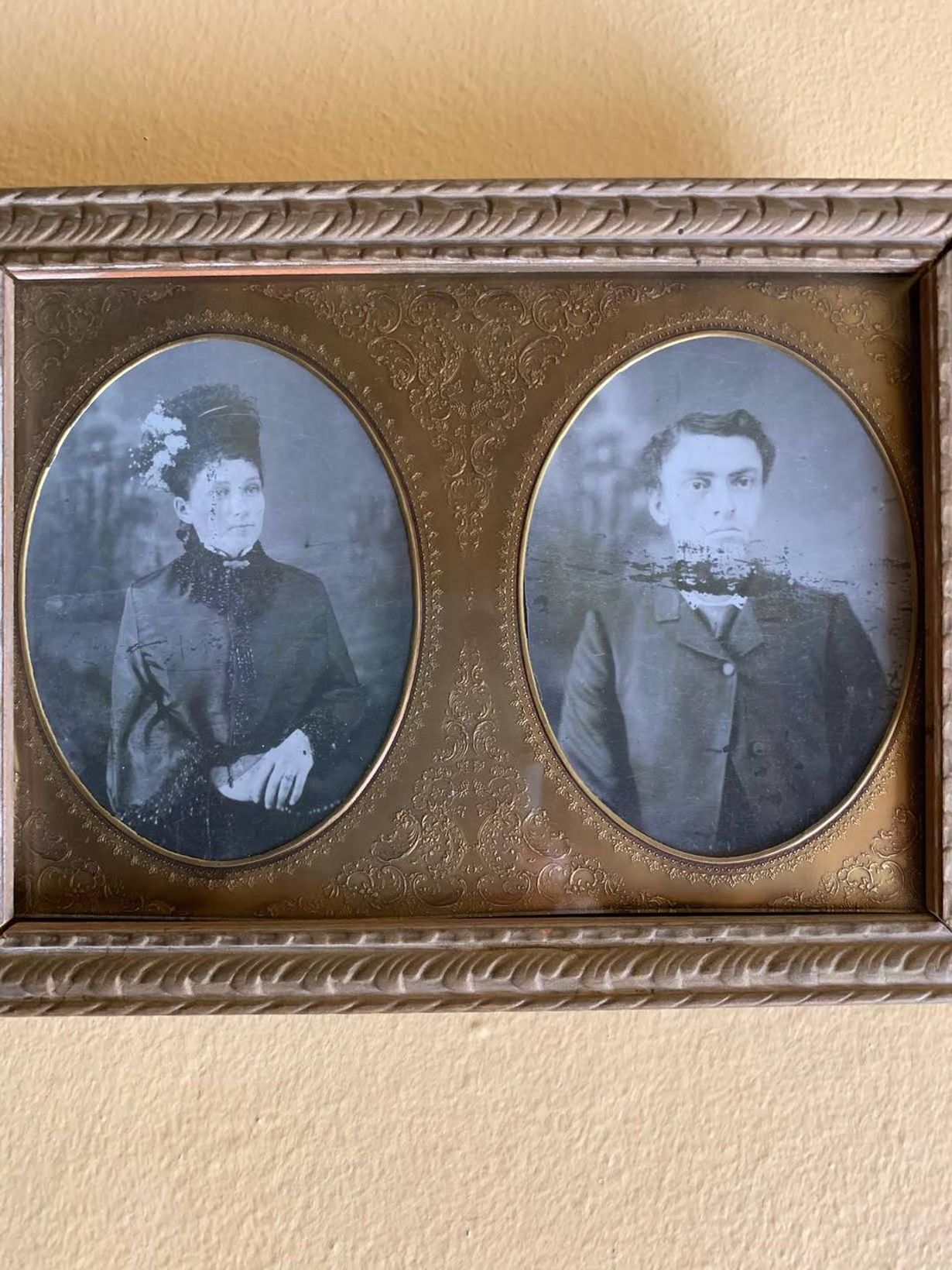 Old photograph of man and woman dressed in bronze picture frame