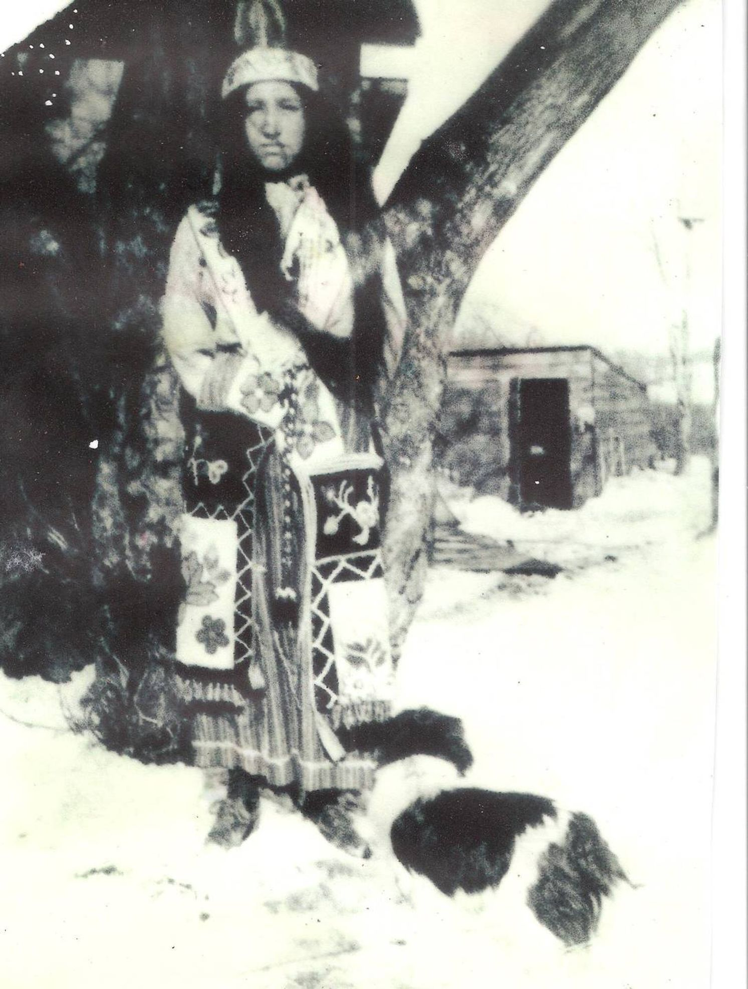 Girl dressed in traditional Ojibwe outfit standing on snow