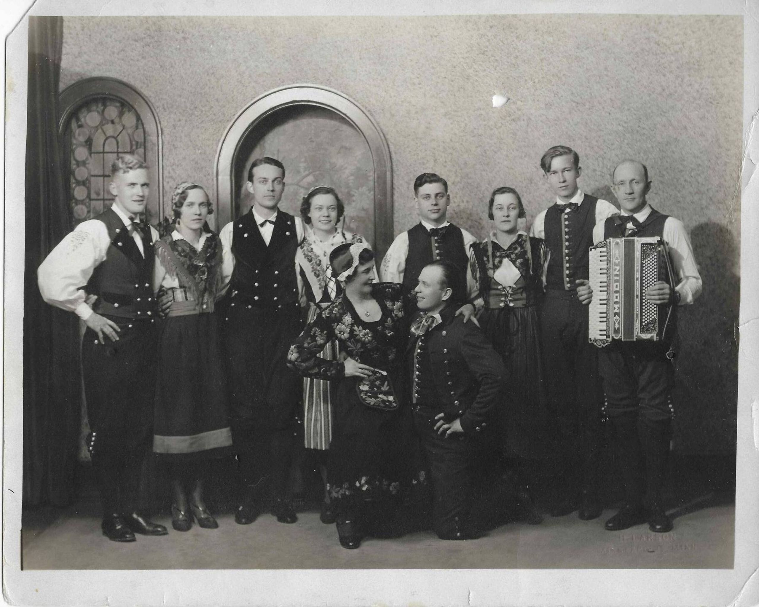 Group of performers standing in formal clothing and holding instruments