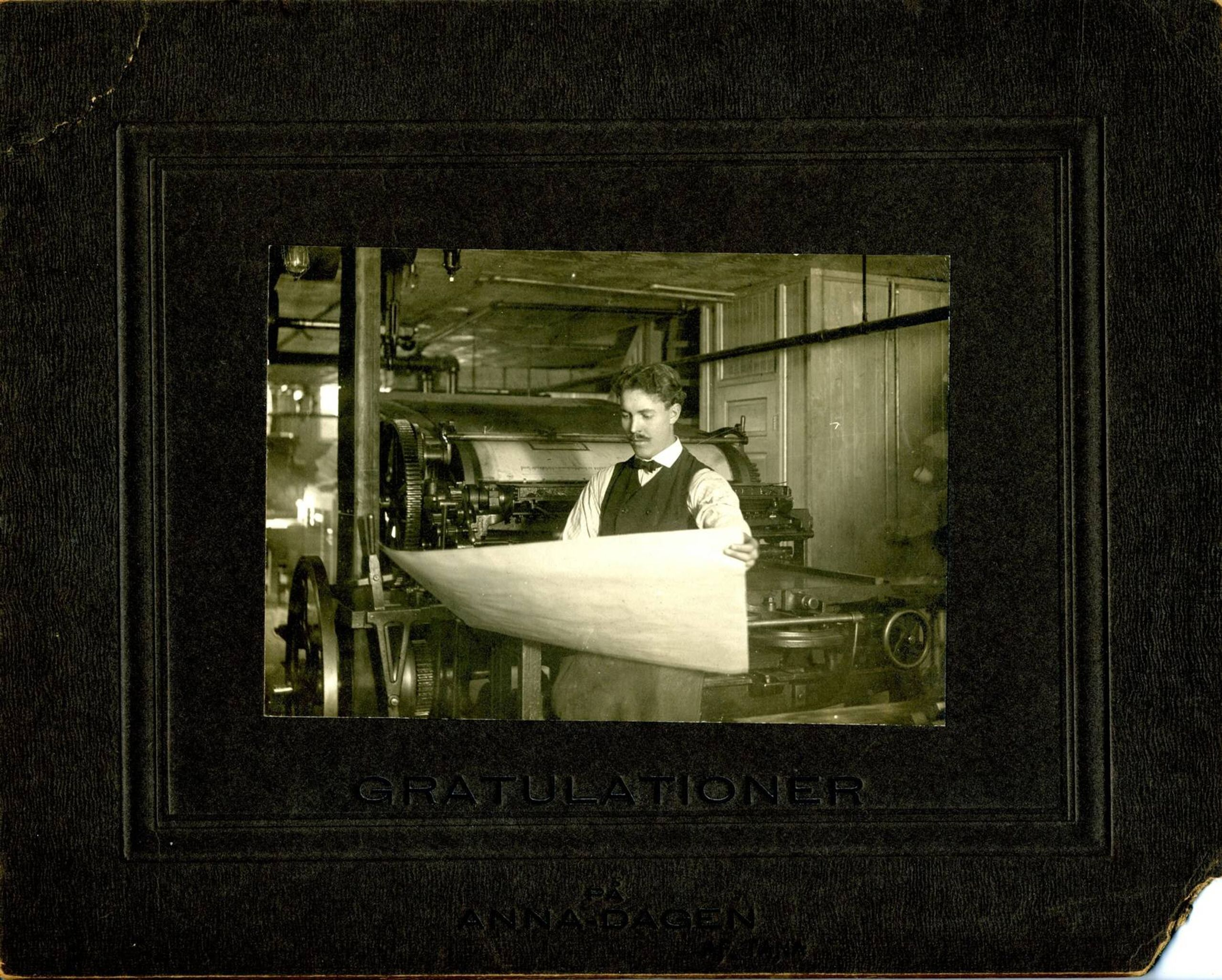 Man dressed formally standing in front of printing roll holding a piece of paper
