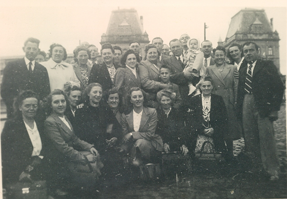 Large gathering of family members crouched down and smiling