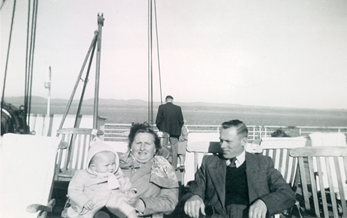 Two parents holding a baby onboard a boat