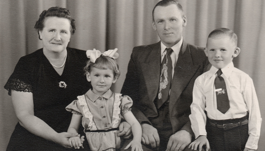 A man, woman, and two children dressed in formal clothes smiling