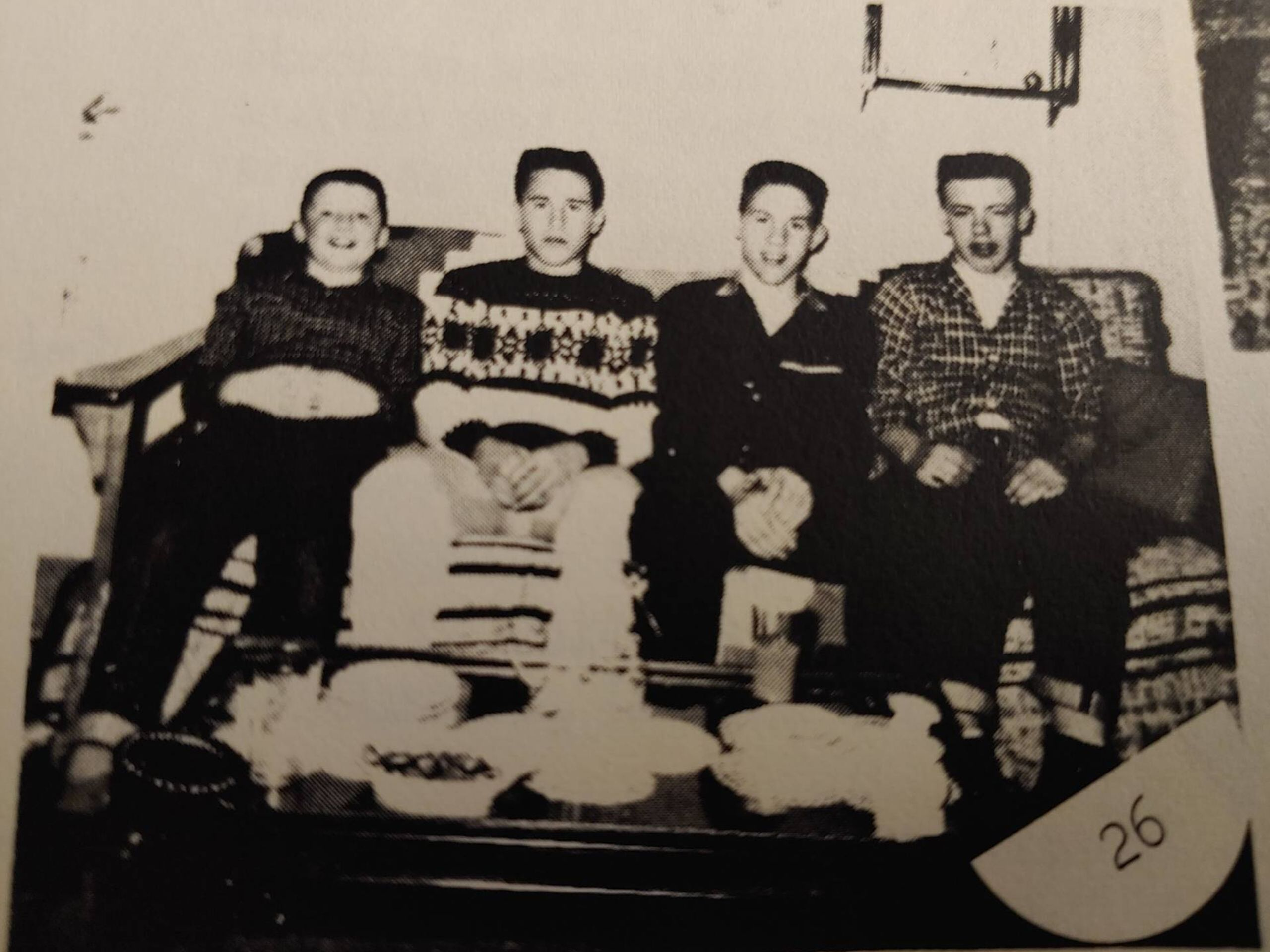 Four children seated on a couch smiling