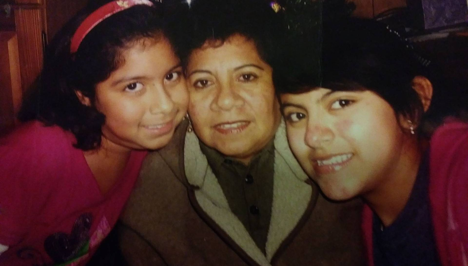 Two younger girls smiling with an older woman wearing a jacket