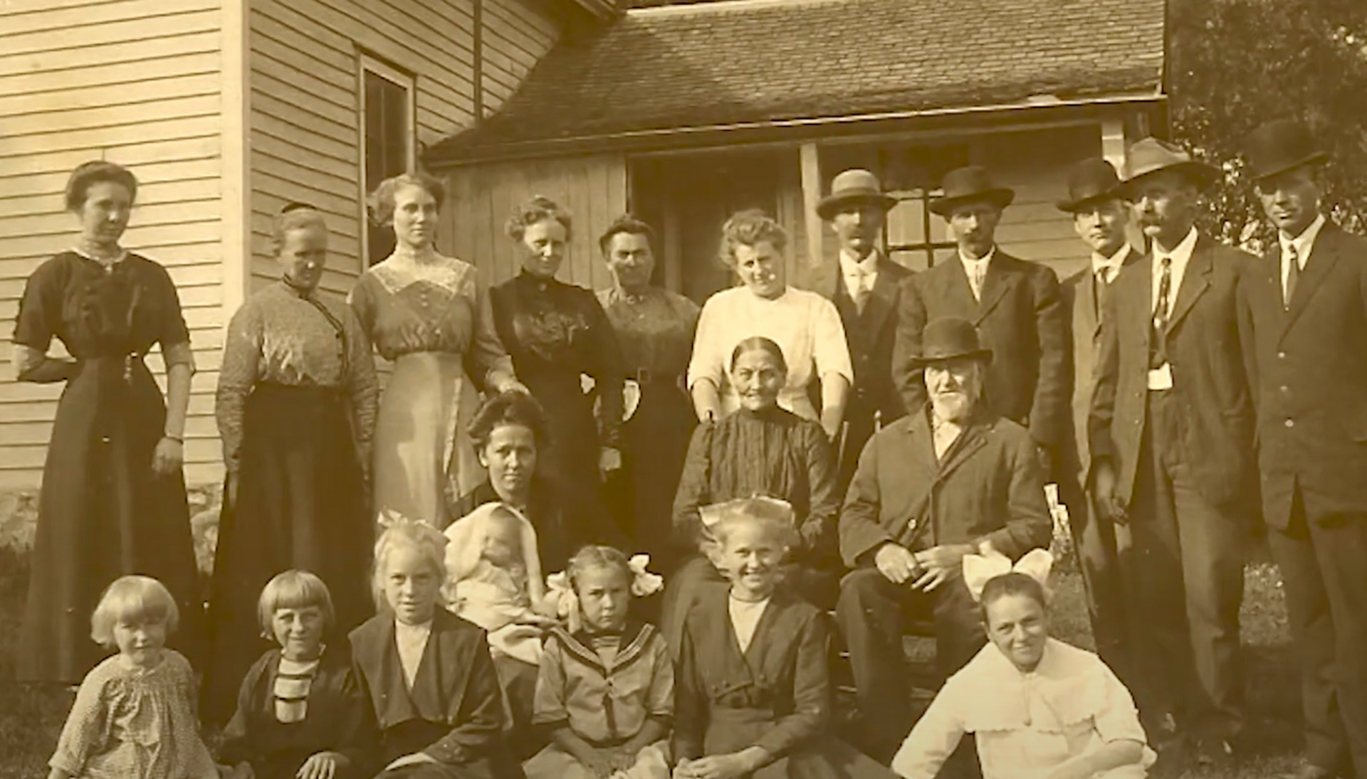 Large family sitting and standing outside by a farmhouse