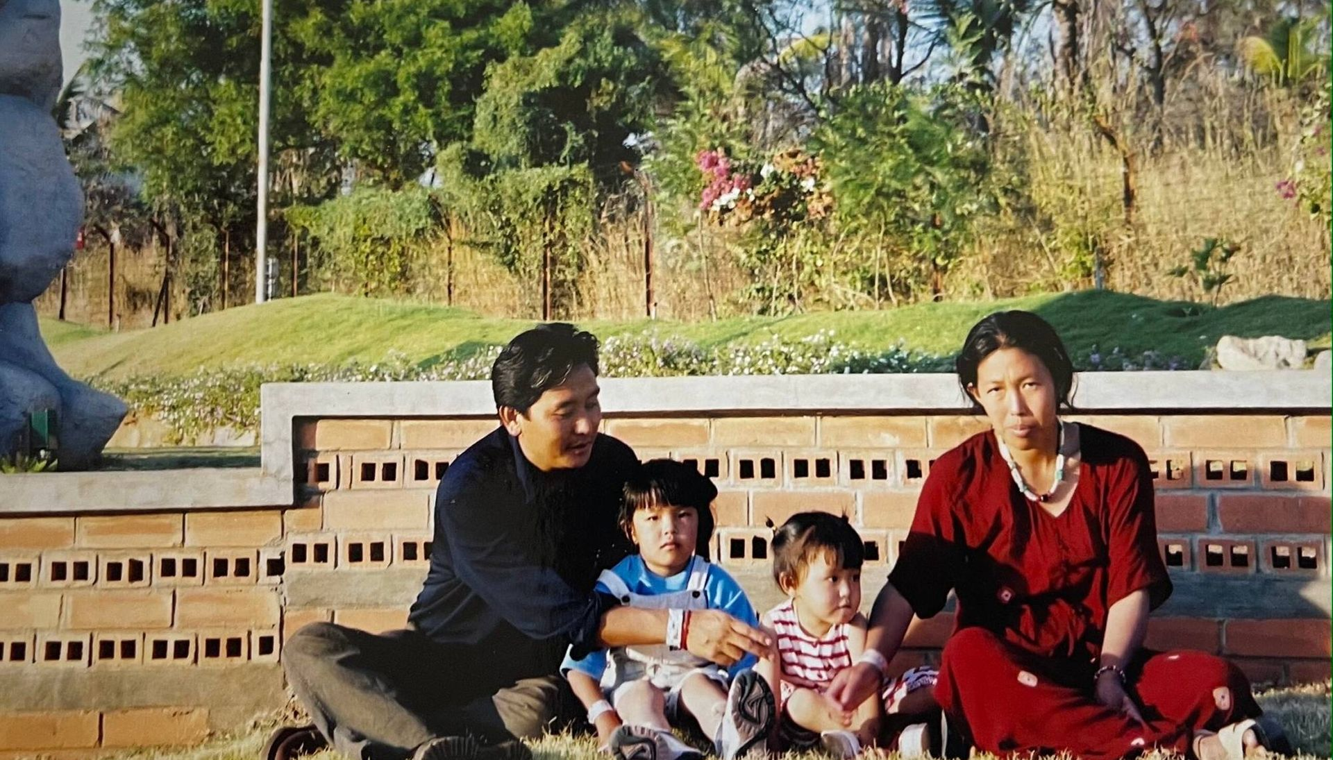 Two parents and two children seated at a park