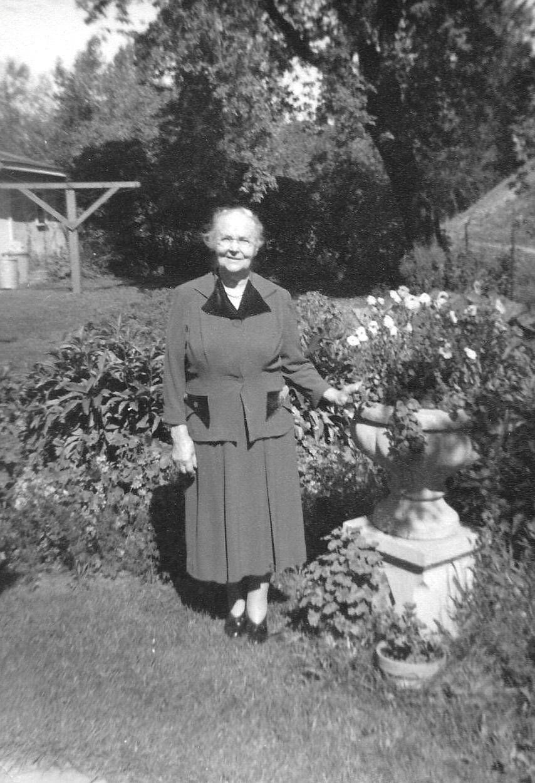 Older woman standing in a garden wearing a dress