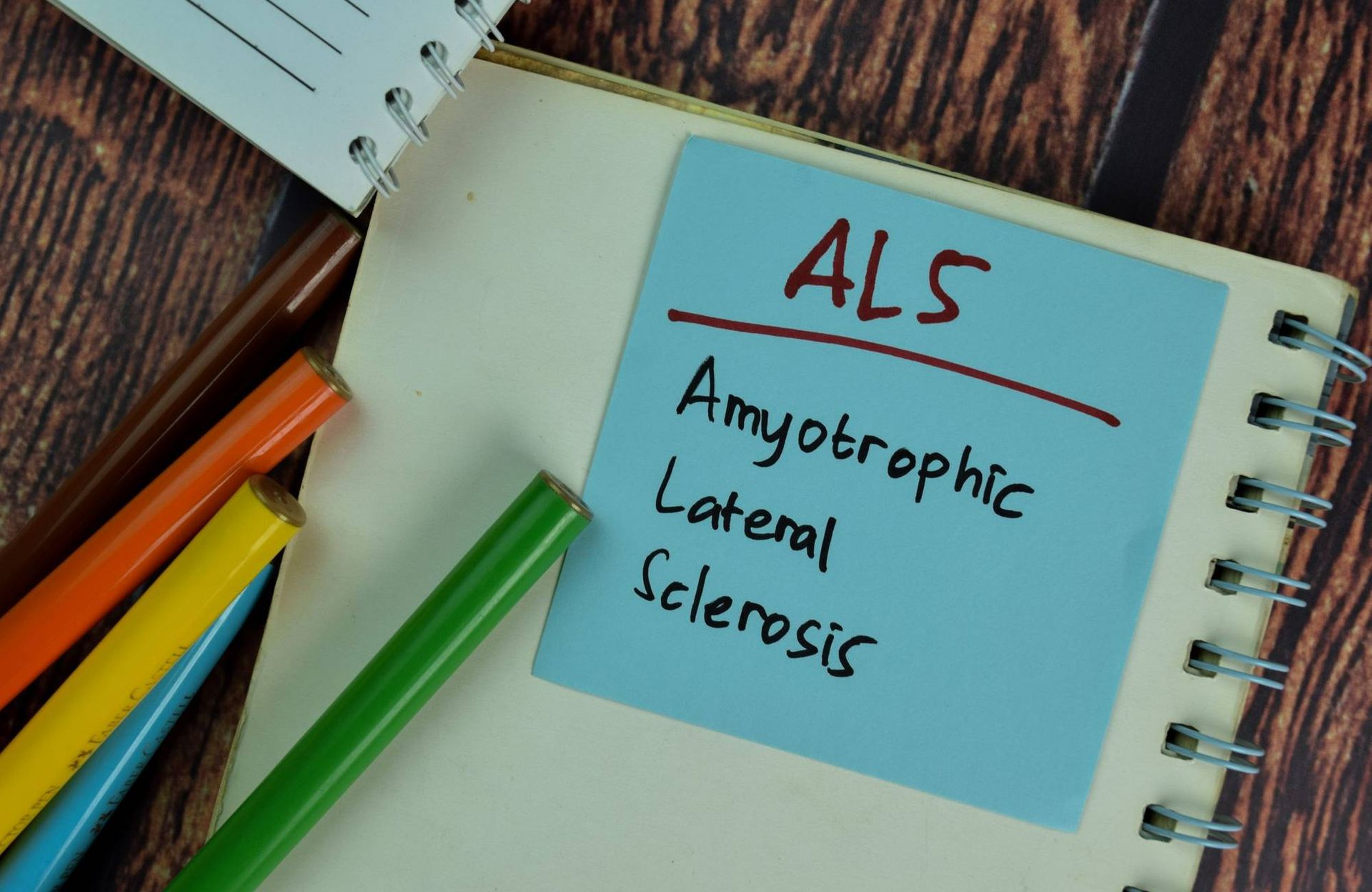 ALS - Amyotrophic Lateral Sclerosis write on sticky notes isolated on Wooden Table.