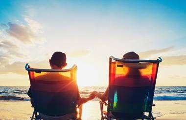 Retired couple sitting on beach