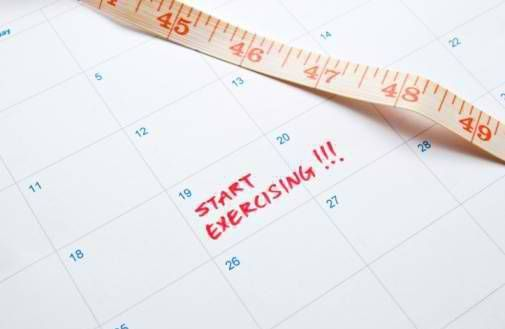 Measuring tape and a notation to start exercising on calendar