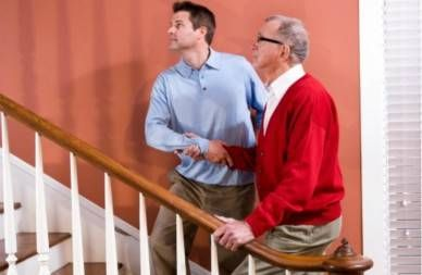 son holding senior father, both looking up at staircase