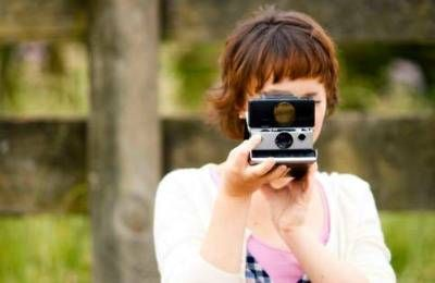 girl taking polaroid with Instant camera