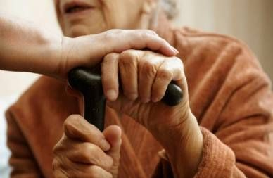 close up of hand placed on elderly woman's hands resting on cane