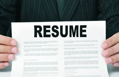 Person holding up a copy of their resume