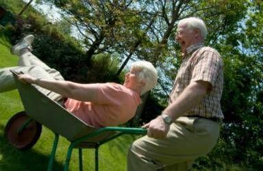 senior man pushing wife in wheelbarrow