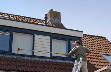 Man with ladder on roof washing exterior of window