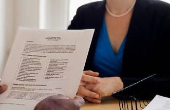 a prospective employer holding a resume facing a woman candidate
