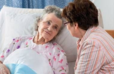 Middle-aged woman comforting her mother in the hospital