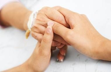 daughter holding her mother's hand on an IV