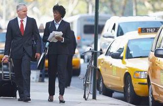 business man and woman walking next to cabs in new york city