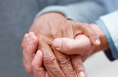 Patient and nurse holding hands