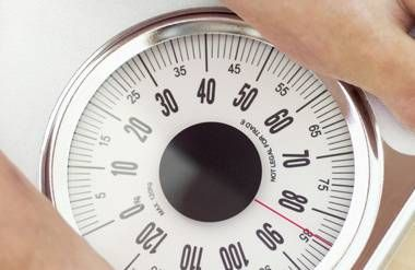 Person checking their weight on a scale