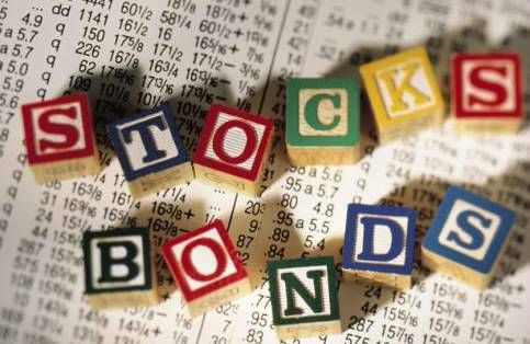 Alphabet blocks spelling stocks and bonds on top of financial paper