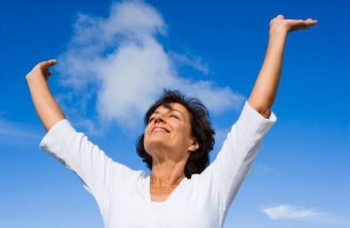 happy woman with arms raised into a 'y'