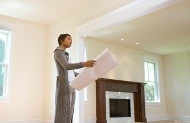 Woman standing in house looking at blueprints
