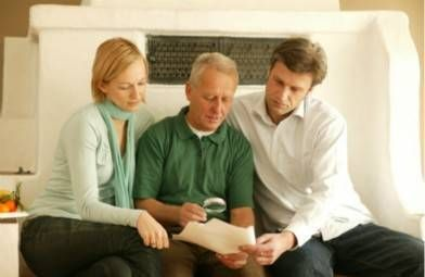 adult siblings reading over paperwork with senior parent